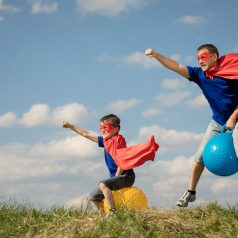 Father and son playing superhero at the day time. People having fun outdoors.They jumping on inflatable balls on the lawn. Concept of friendly family.